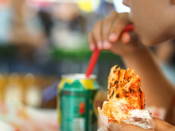 menino alimentado a pão de fast-food com sua mão e, também, a bebida - junk food - fotografias e filmes do acervo