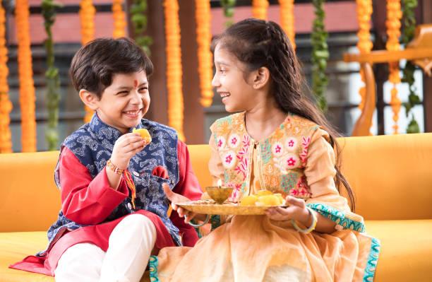 Boy feeding sweet food to his sister stock photo