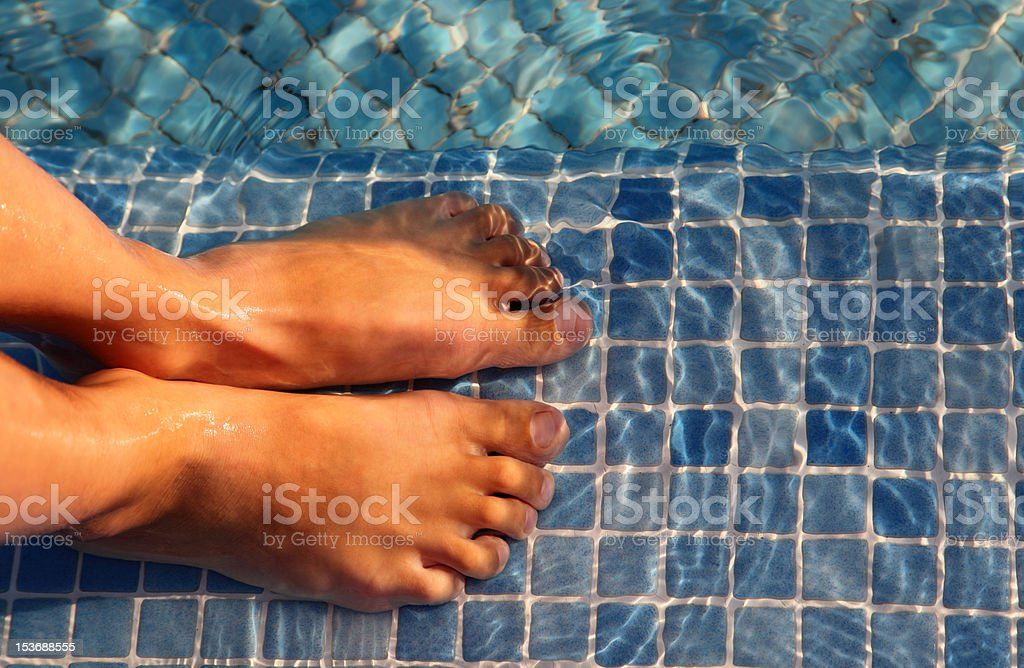 boy feet are jointed and putted in water of swimming-pool stock photo