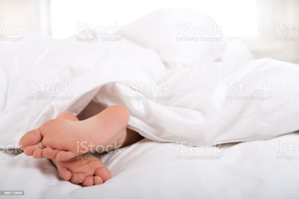 Boy feet under sheet stock photo