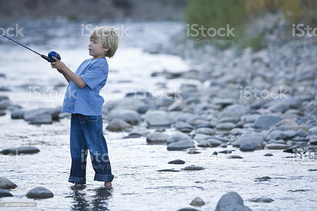 Boy (6-7) fishing in river Lizenzfreies stock-foto
