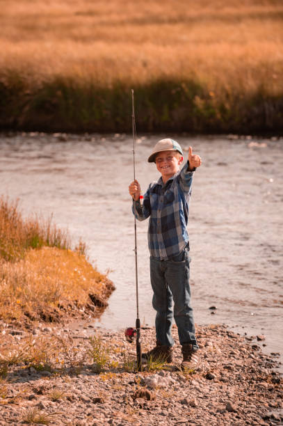 Boy Fishing In The Mountains stock photo