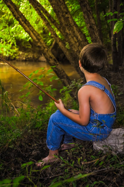 A Boy Fishing A boy sitting down on a rock fishing bib overalls boy stock pictures, royalty-free photos & images