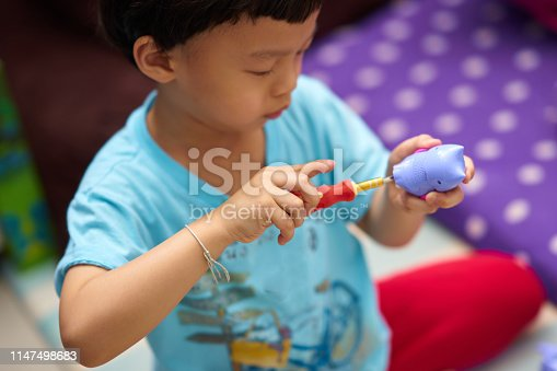 540396126istockphoto Boy fixed his toy by screw driver in house 1147498683