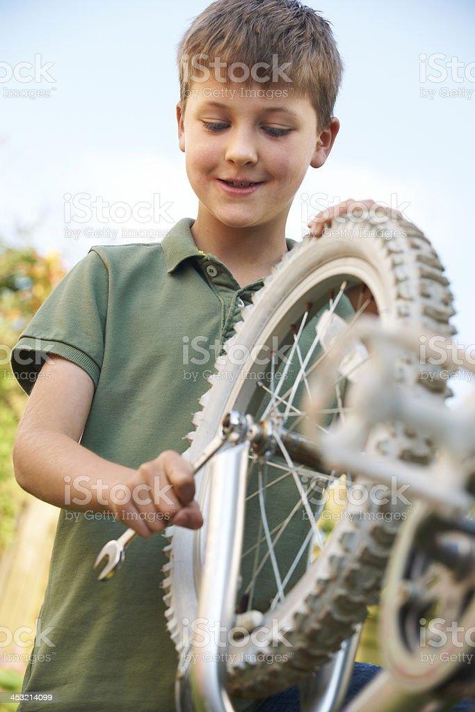 Boy Fixing Wheel Of Bike royalty-free stock photo