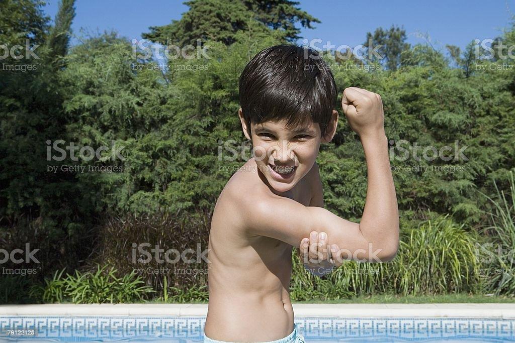 Boy flexing muscles 免版稅 stock photo