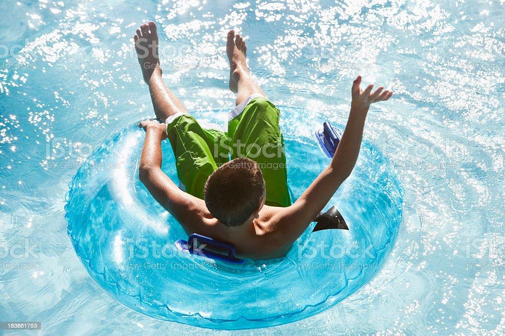 Boy floating on innertube stock photo