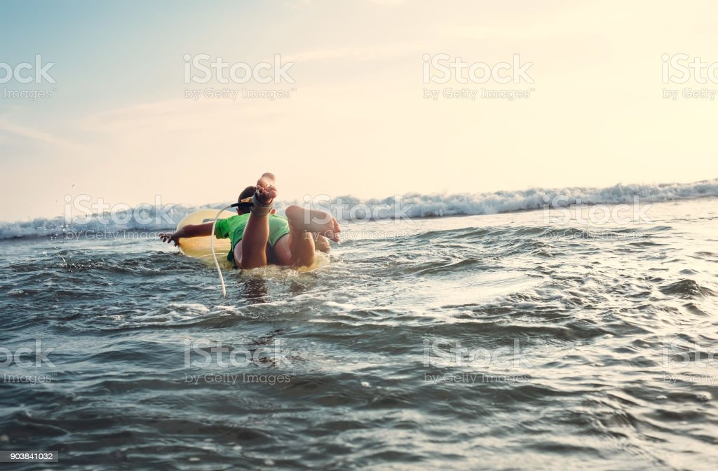Boy floats on surf board. Beginner surfer, first lessons stock photo