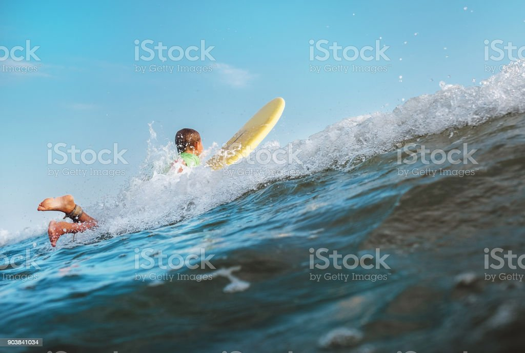 Boy floats on surf board over the wave crest stock photo