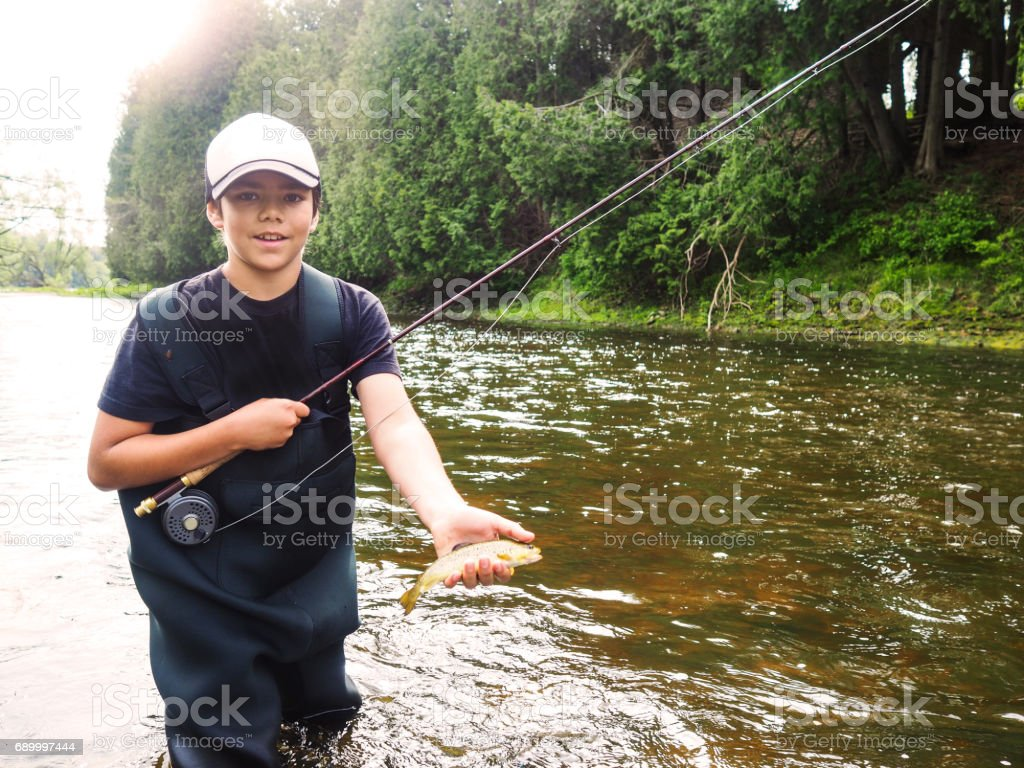 Boy fly-fishing on a river stock photo