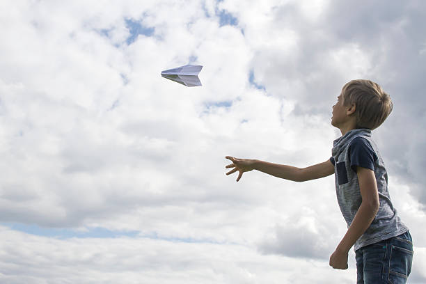 Boy flying a paper plane against blue sky - Photo