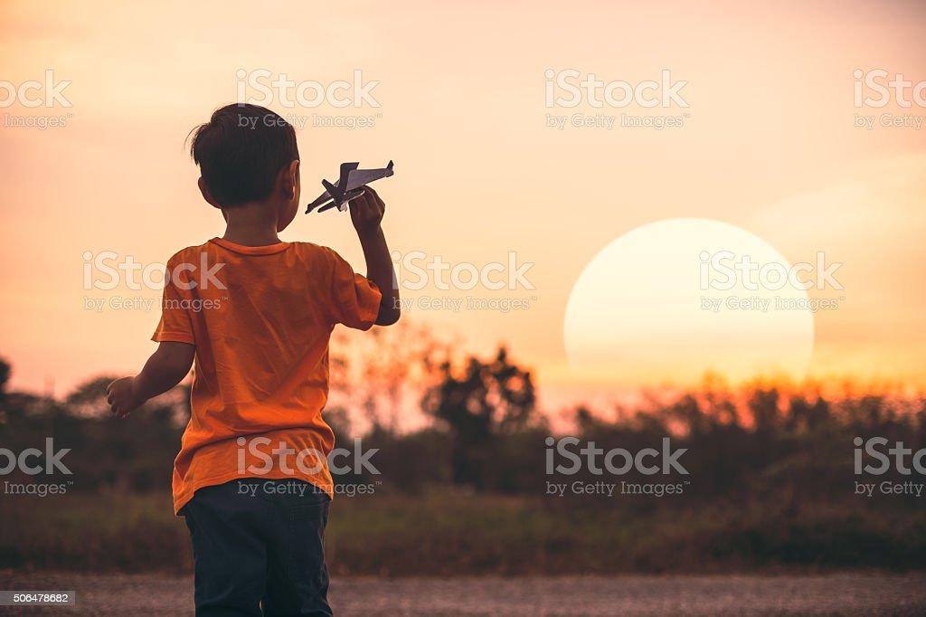 Boy flying airplane stock photo