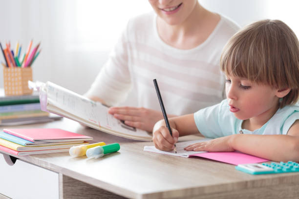 boy focusing on homework - homework stock photos and pictures