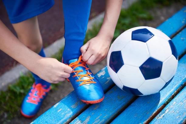 jungen fußball binden schnürsenkel schuhe auf bank - sitzbank schuhe stock-fotos und bilder