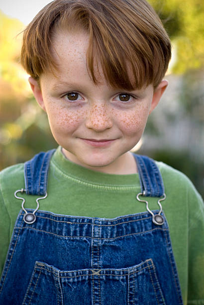 Boy Freckle Face, Smiling Child Redhead in Overalls Outdoors