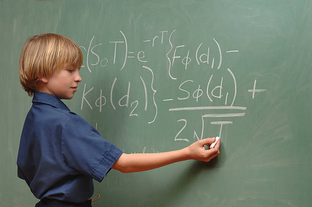 Boy Genius Nine year old boy doing advanced math on a chalkboard child prodigy stock pictures, royalty-free photos & images