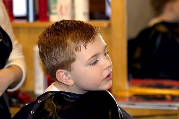 boy gets haircut stock photo