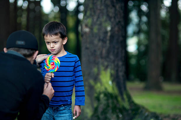 Boy getting offered a piece of candy by a stranger Boy getting offered a piece of candy by a stranger stranger stock pictures, royalty-free photos & images