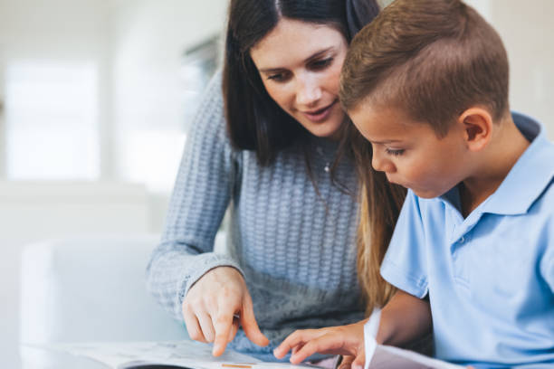 boy getting tutored with school assignment Young boy receiving one on one help with assignment. elementary school teacher stock pictures, royalty-free photos & images