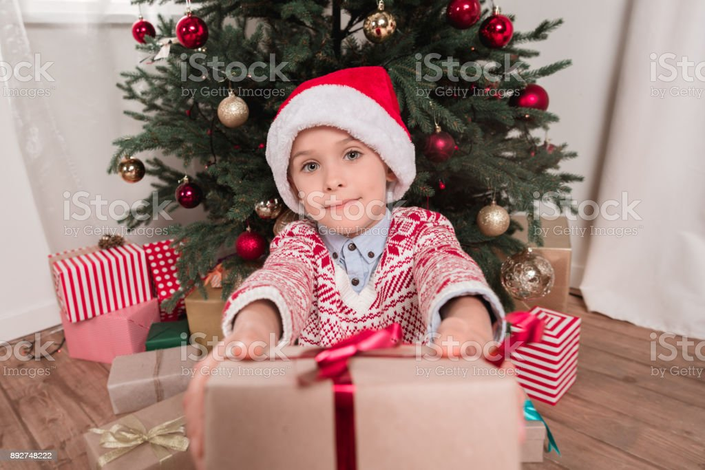 boy giving christmas present to camera stock photo