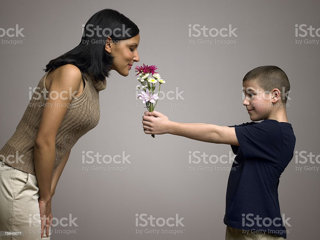Boy giving flowers to mother