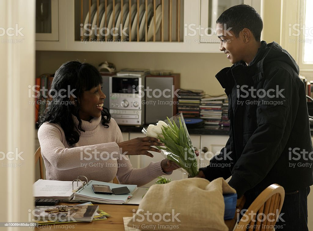 Boy (12-13) giving mother bunch of flowers at home 免版稅 stock photo