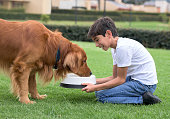 Happy boy giving water to his dog - animal lover concepts