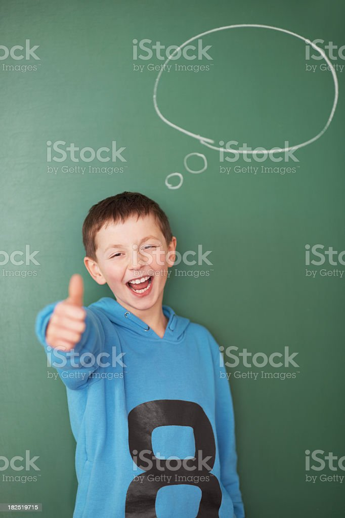 Boy giving you a thumbs up sign against chalkboard royalty-free stock photo