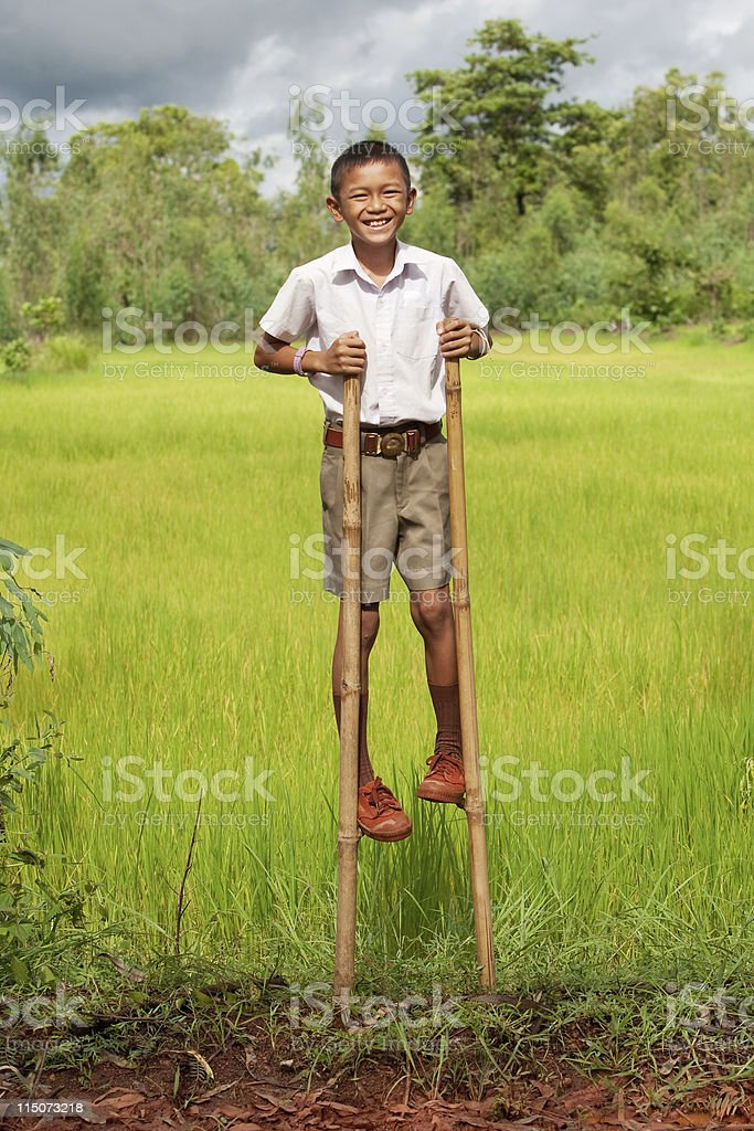 Boy goes on stilts stock photo