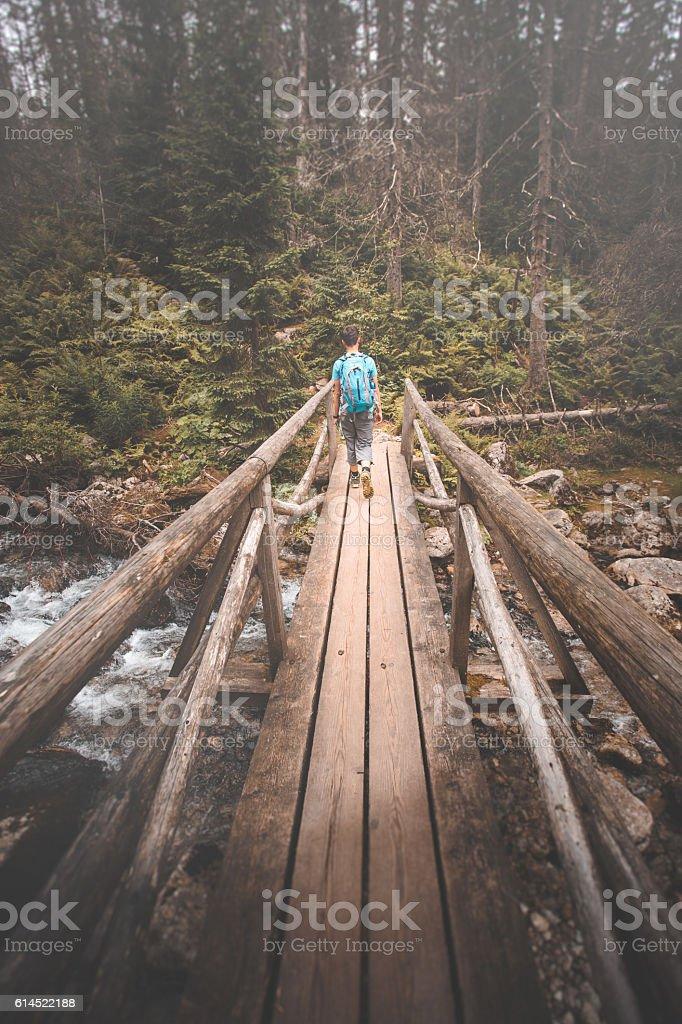 Boy going over bridge stock photo