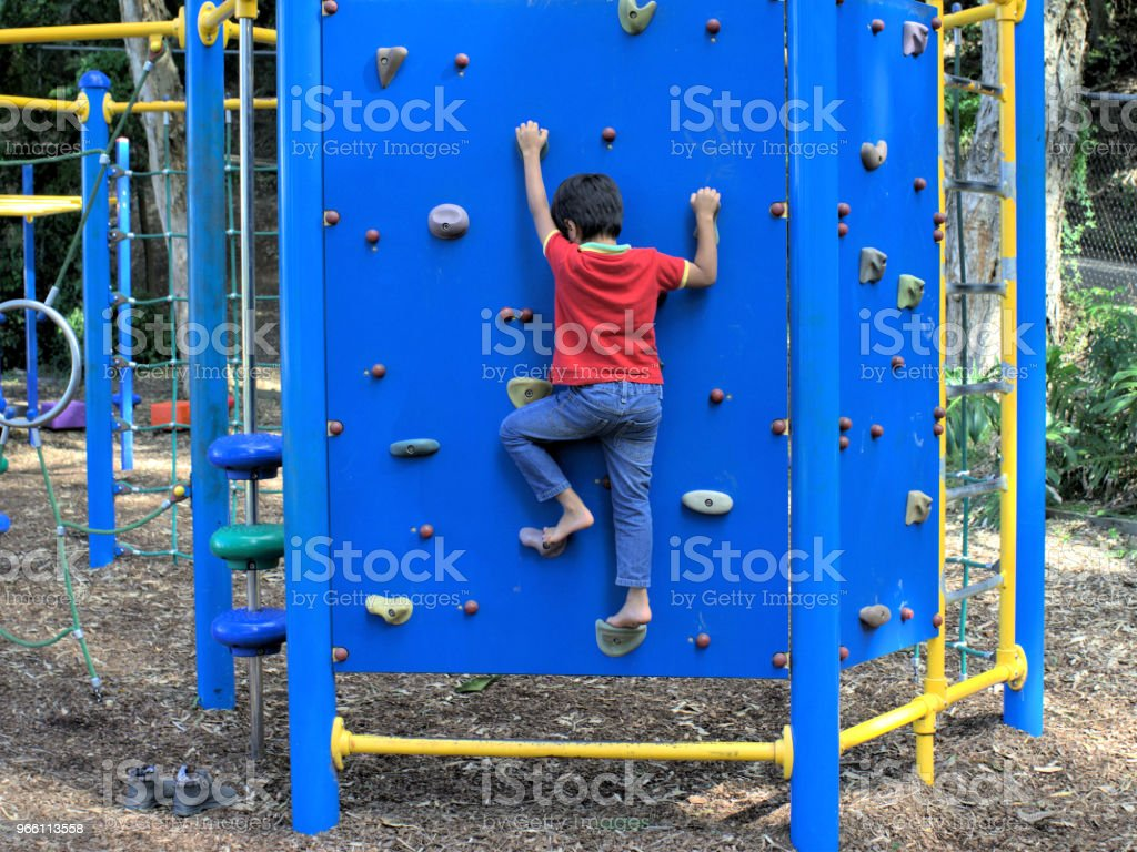 Boy going up on climbing wall - Royalty-free Activity Stock Photo