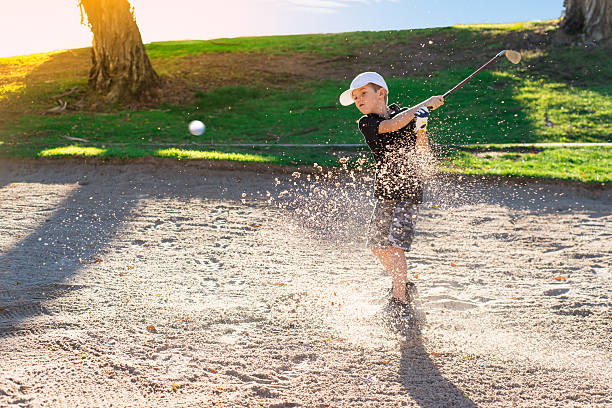 Boy Golfer Hitting Out A Sand Bunker stock photo