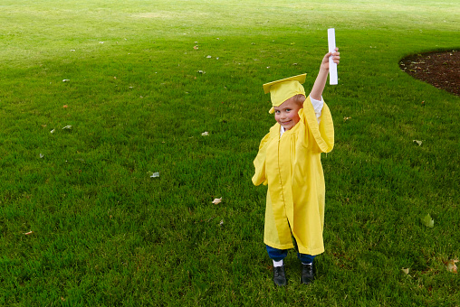 Young, Caucasian boy is dressed in a yellow graduation gown, holding up his diploma with a green grass background