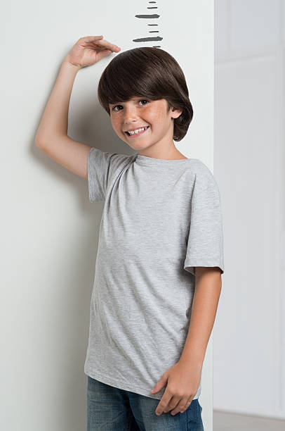 boy growing tall and measuring himself - height measurement stock photos and pictures