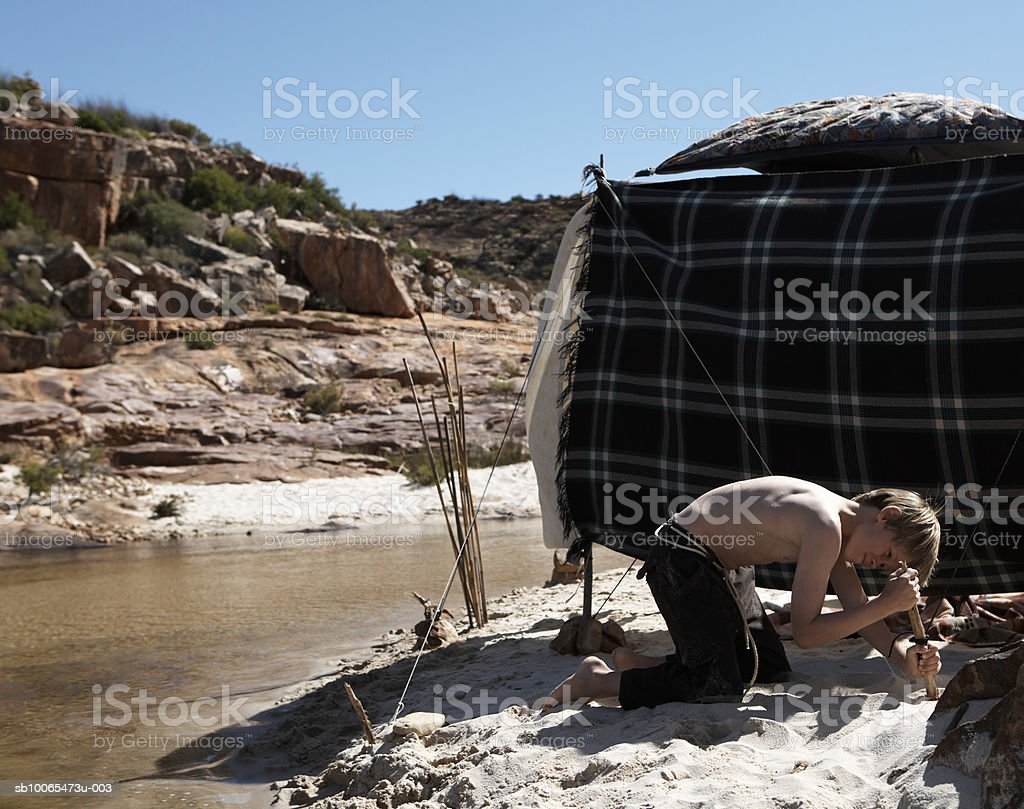Boy (11-13) hammering tent peg, side view royalty-free stock photo
