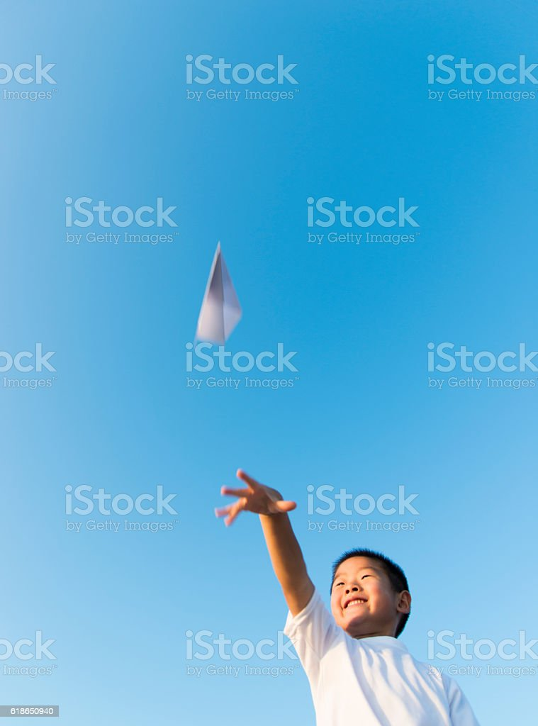 Boy hand holding a paper plane with view of sky - foto de stock