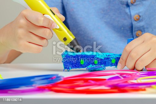 1082038948 istock photo Boy hands creating with 3d printing pen new object 1189109214