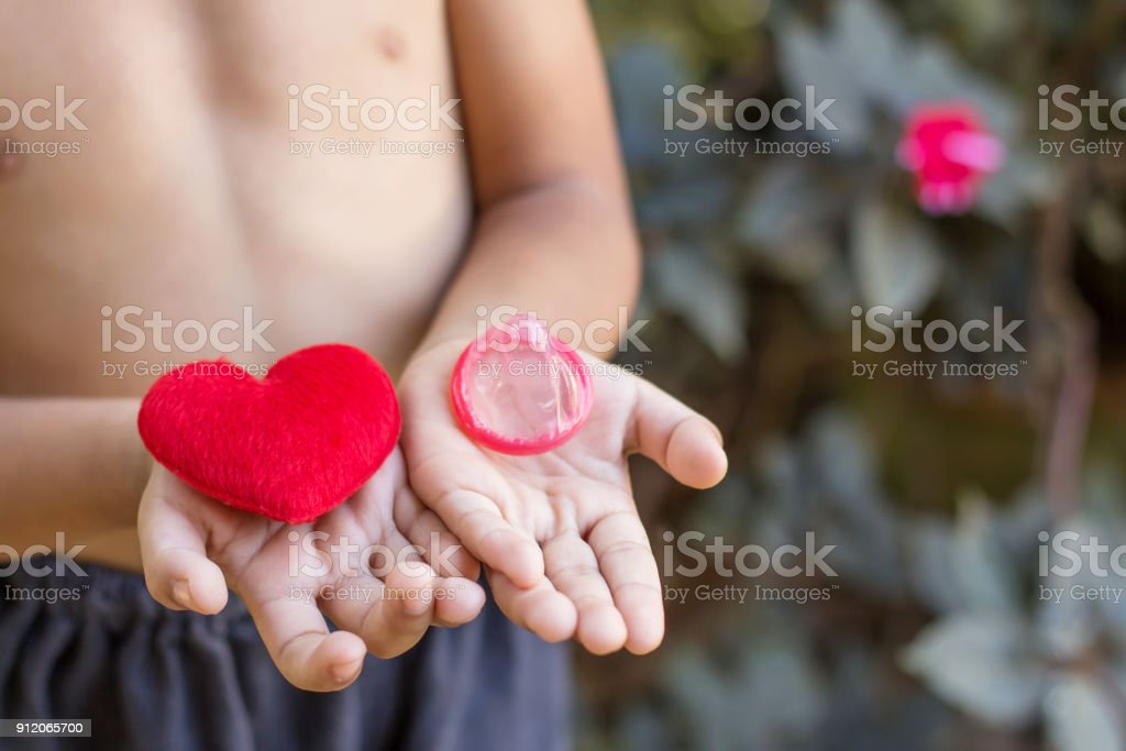 Boy Hands Holding Red Heart Condom For Prevention Of Sexually