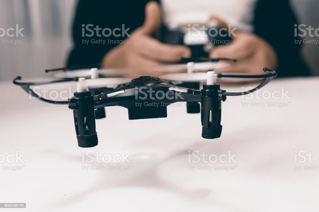 Boy hands with remote control flying small drone toy indoors. stock photo