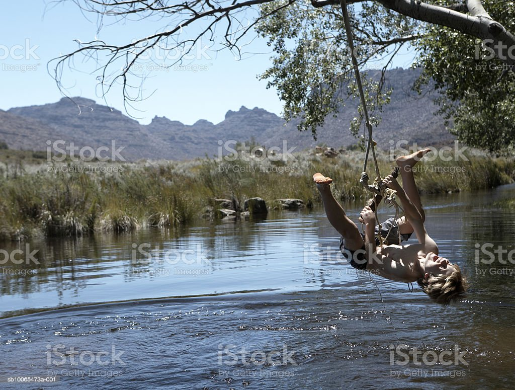 Boy (10-11) hanging from tree upside down by stream royalty-free stock photo