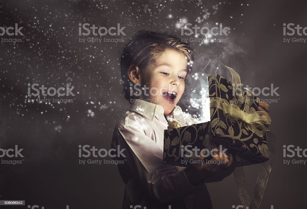 Boy Happy while opening Magic Gift, lights and Stars Little Boy Happy with a Magic Gift, light beams and Stars coming out of a half opened luxurious gift box 4-5 Years Stock Photo