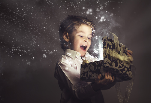 Boy Happy While Opening Magic Gift Lights And Stars Stock Photo - Download Image Now