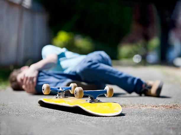 Boy has accident on Skateboard stock photo