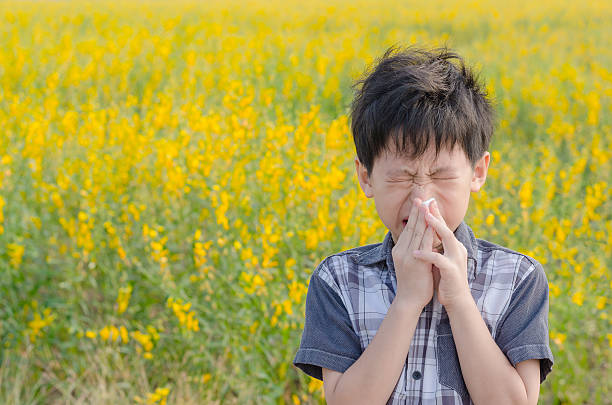 boy has allergies from flower pollen stock photo