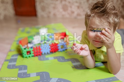 489225417 istock photo Boy has fun and plays children's toys in the room 1210129404
