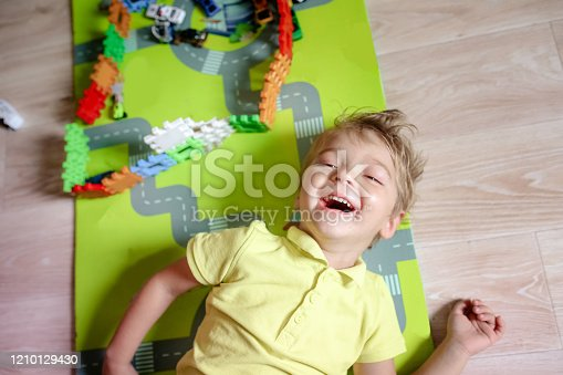 489225417 istock photo Boy has fun and plays children's toys in the room 1210129430