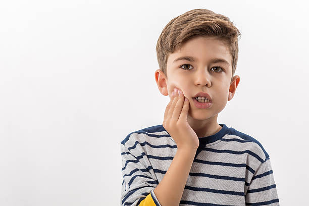 Boy having a toothache holding his face with his hand stock photo