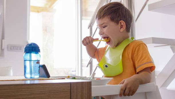 junge mit frühstück - kinderstuhl und tisch stock-fotos und bilder