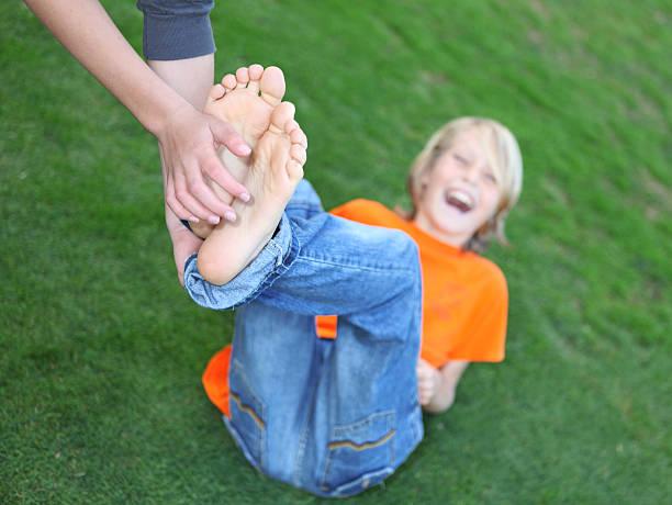 junge, die füße tickled (persönliche anfrage), geringe tiefenschärfe zu fuß - jungen stock-fotos und bilder