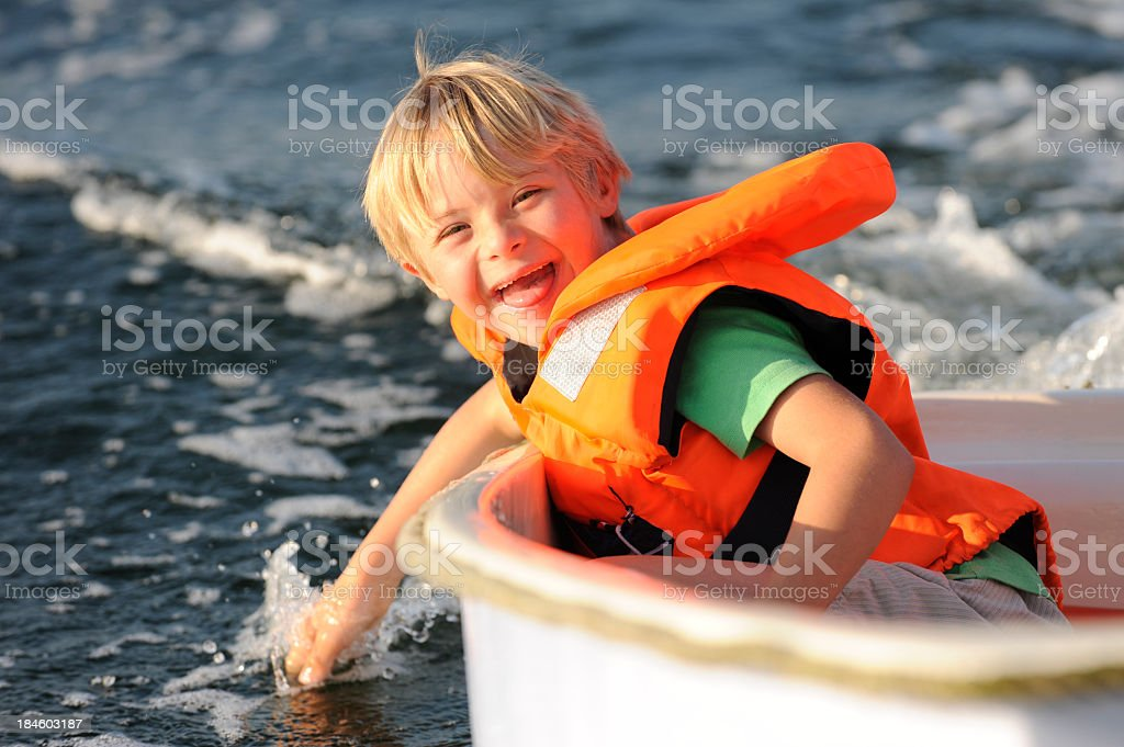 Boy having fun in a small boat stock photo
